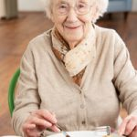 Elderly woman smiling, eating lunch