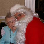 Man dressed as Santa hugging woman at a Christmas Party at Ledgeview Assisted Living