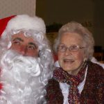 Man dressed as Santa hugging smiling woman at a Christmas Party at Ledgeview Assisted Living